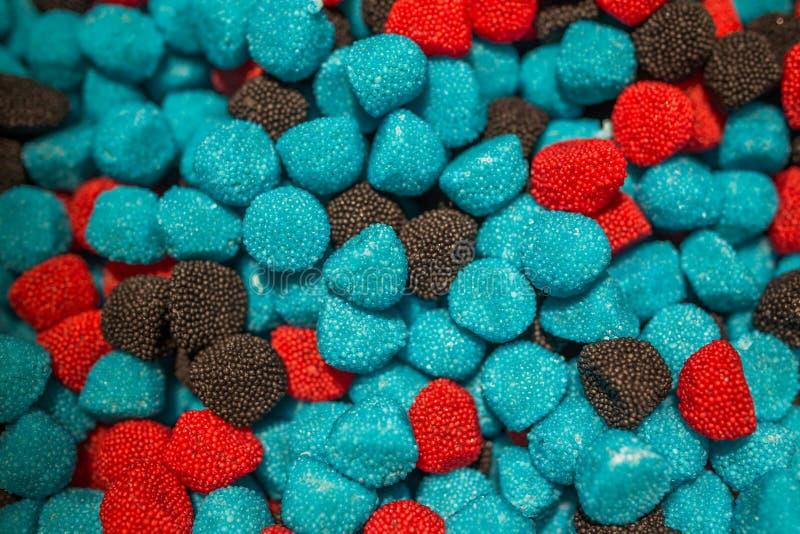 Blåa svarta och röda godisar i form av hallon och björnbär royaltyfria foton