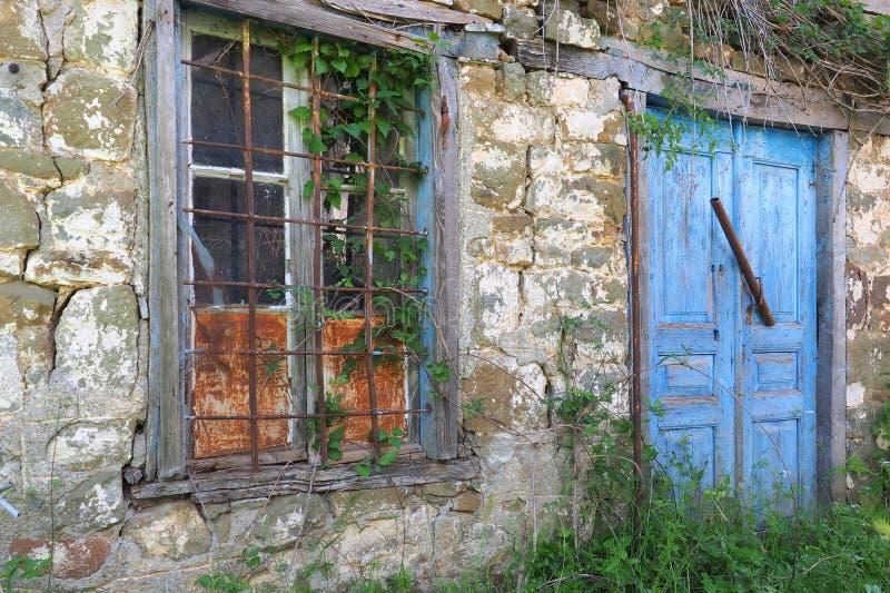 Blåa trädörrar på grekiskt byhus för gammal sten royaltyfri bild
