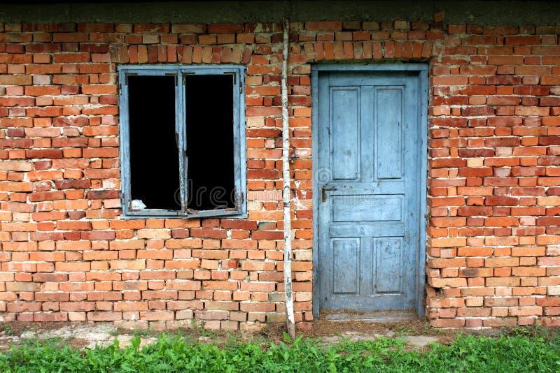 Blåa trähusdörrar med urblekt färg som monteras på väggen för röd tegelsten bredvid bruten gammal fönsterram utan exponeringsglas arkivbild