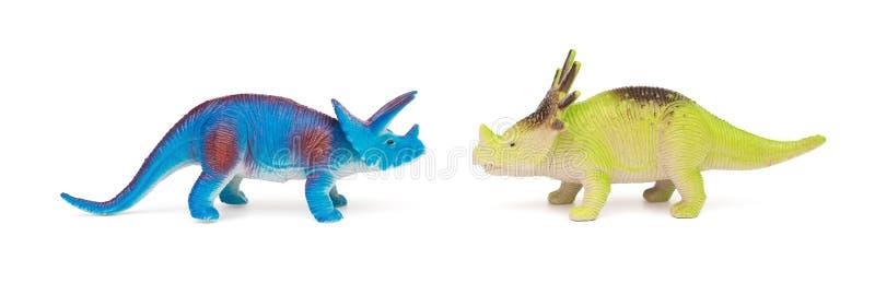 Blåa triceratops- och gräsplanstyracosaurusleksaker på vit bakgrund arkivbild