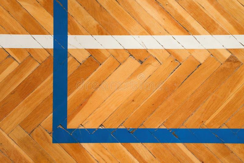 Blåa vita linjer Det slitna trägolvet av sportkorridoren med den färgrika markeringen fodrar ut royaltyfria bilder