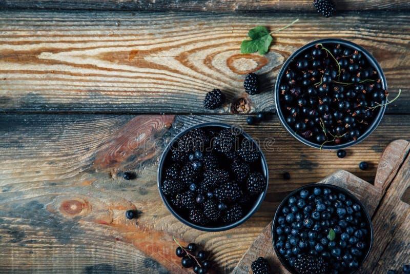 Blåbär björnbär, svart vinbär i bunkar på en träbackgro arkivfoton