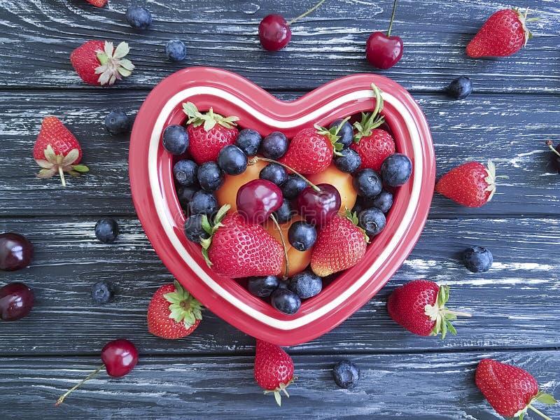 Blåbär hjärta för platta för körsbärsröd säsongsbetonad ingrediens för jordgubbe sund på gammalt svart trä royaltyfria foton