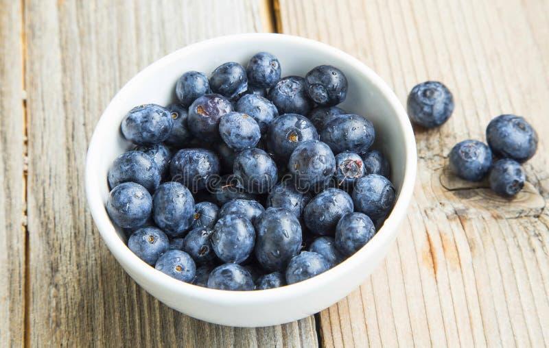 Blåbär i en bunke, sunda bärfrukter i den vita bunken royaltyfri fotografi