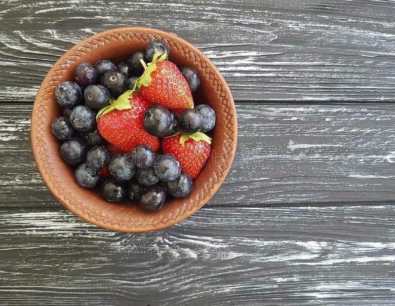 Blåbär jordgubbeantioxidant på en gammal svart träsommar arkivbilder