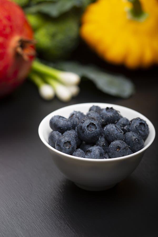 Blåbär med droppar av vatten i en bunke med en bakgrund av grönsaker, frukt och på en svart träyttersida arkivbilder