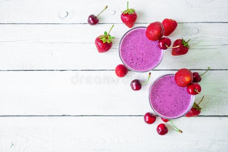 Blåbär och jordgubbemilkshake och bär på den vita trätabellen Ny naturlig smoothie Lekmanna- lägenhet, bästa sikt royaltyfria foton