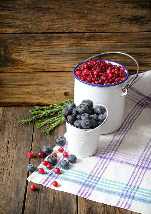 Blåbär och tranbär i emaljerad hink på en träbackg arkivfoton