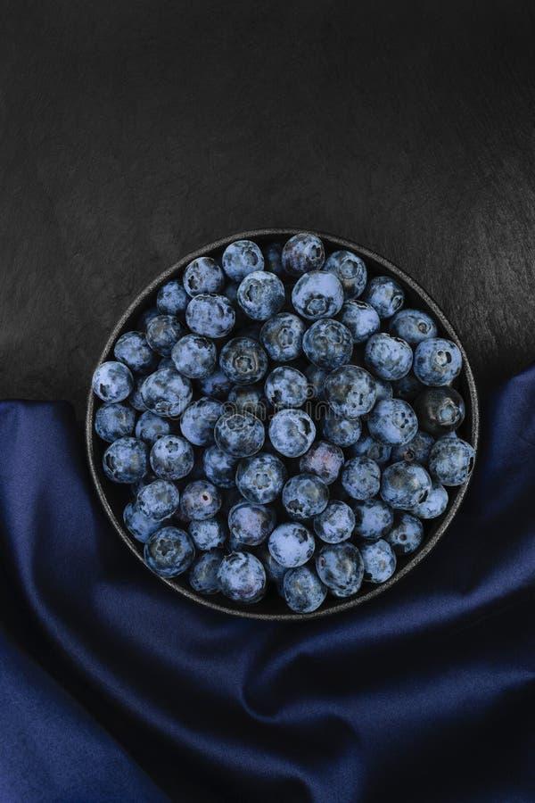 Blåbär på blått tyg och svart stenar bakgrund arkivbild