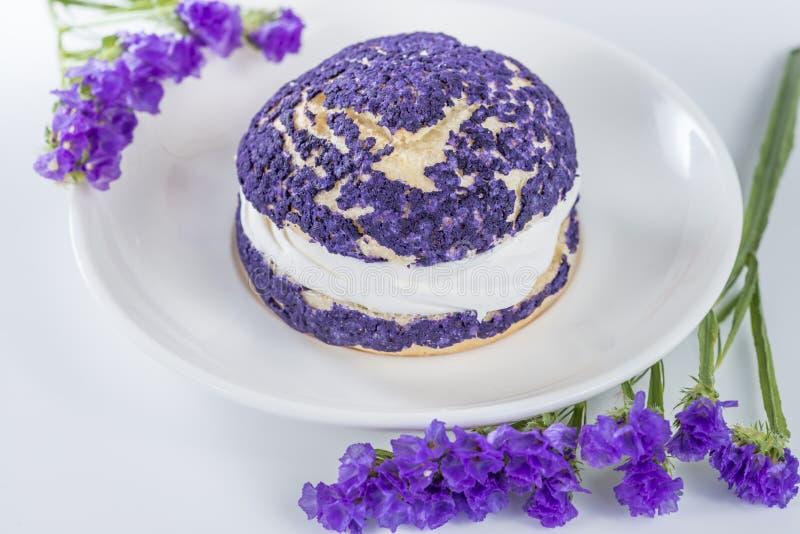 Blåbärkakashu som dekoreras med purpurfärgade blommor av staticen royaltyfri fotografi