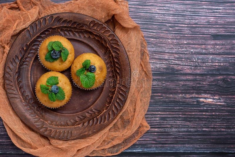 Blåbärmuffin i brun platta på mörk träbakgrund Top beskådar Med kopiera utrymme royaltyfri bild