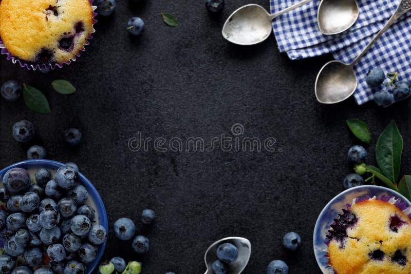 Blåbärmuffin och nya blåbär på en svart bakgrund med kopieringsutrymme, bästa sikt arkivbild