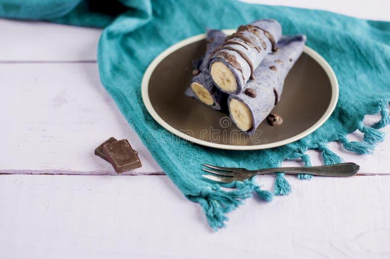 Blåbärpannkakor som är välfyllda med den hela bananen som slås in i ett rör och hälls med choklad royaltyfri fotografi