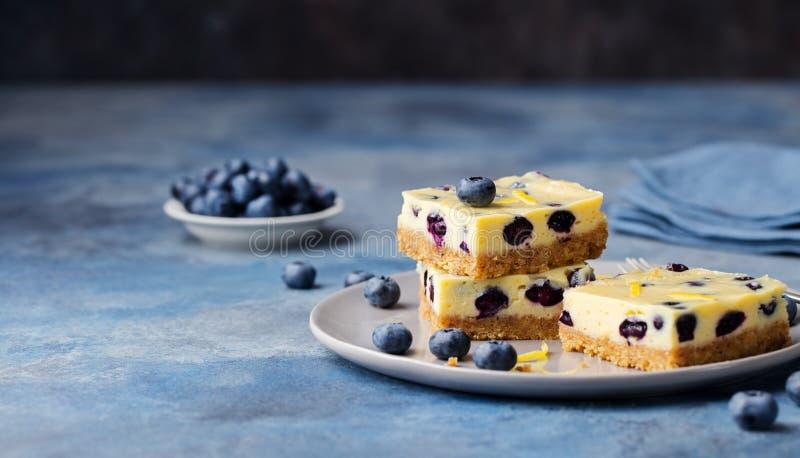 Blåbärstänger, kaka, ostkaka på en grå platta på bakgrund för blå sten royaltyfria bilder