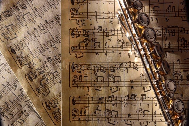 Blåsa flöjt på gammal handskriven composi för bästa sikt för notblad horisontal royaltyfria bilder