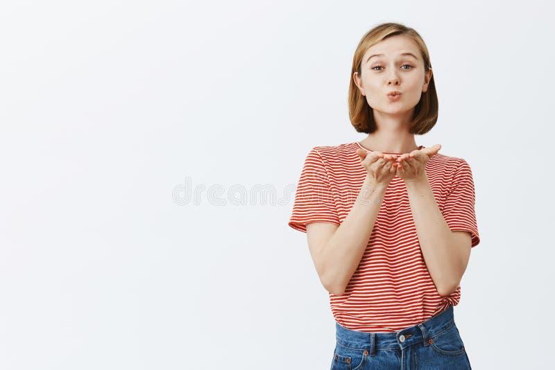 Blåsa kyssen för alla ensamma personer i värld Den charmiga och lyckliga flickan med blont kort hår som rymmer gömma i handflatan arkivfoto