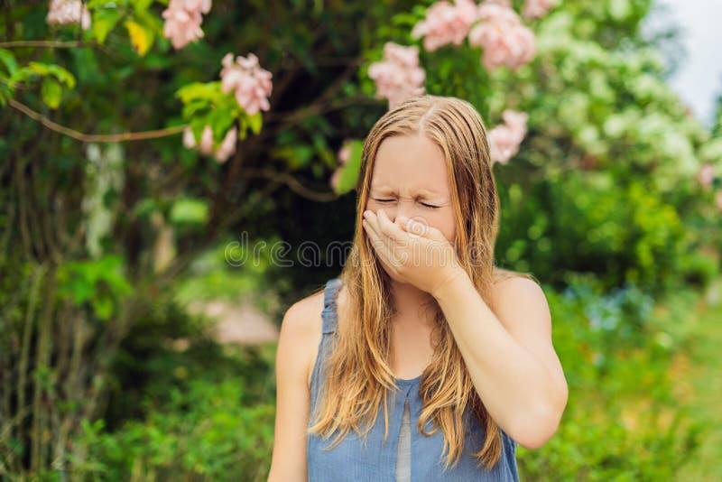Blåsa näsa för ung nätt kvinna framme av att blomma trädet Vårallergibegrepp arkivfoton