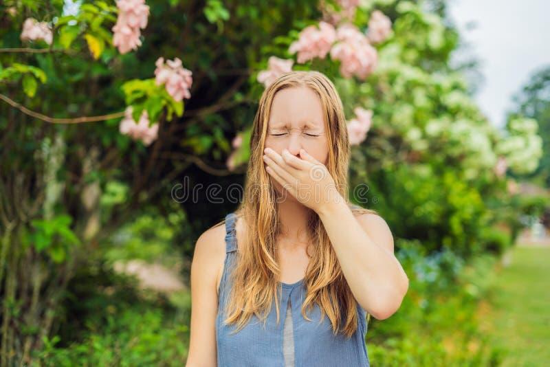 Blåsa näsa för ung nätt kvinna framme av att blomma trädet Vårallergibegrepp royaltyfri foto