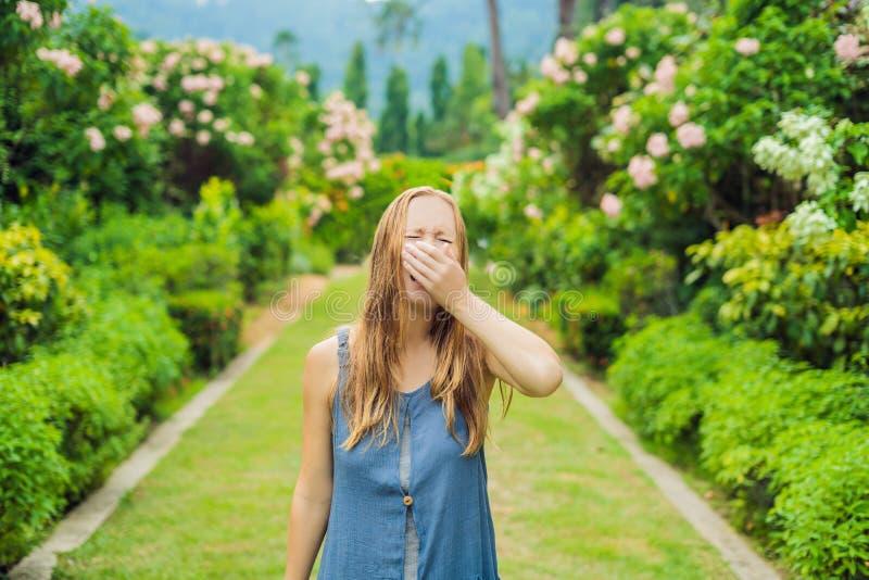 Blåsa näsa för ung nätt kvinna framme av att blomma trädet Vårallergibegrepp arkivbild