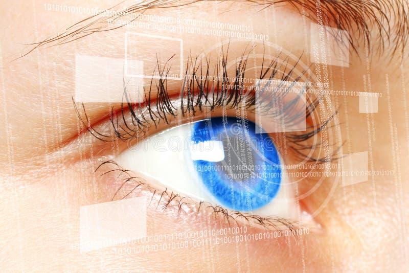 Blått öga för kvinna som ser på den digitala faktiska skärmen royaltyfri foto