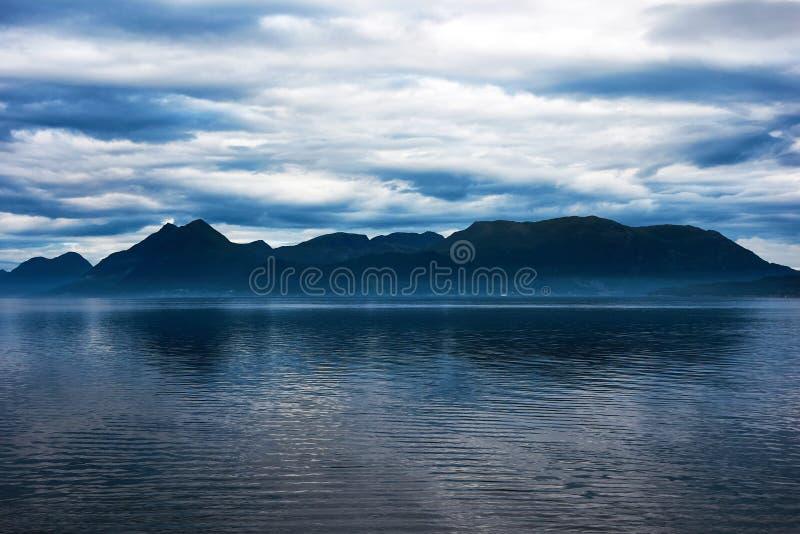 Blått berg över en fjord arkivbild