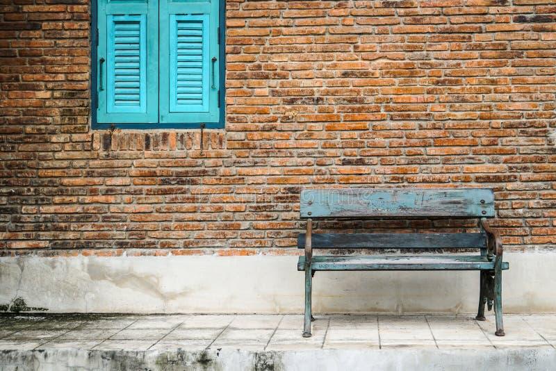 Blått fönster, lantlig bänkstol vid yttersida för tegelstenvägg royaltyfri foto
