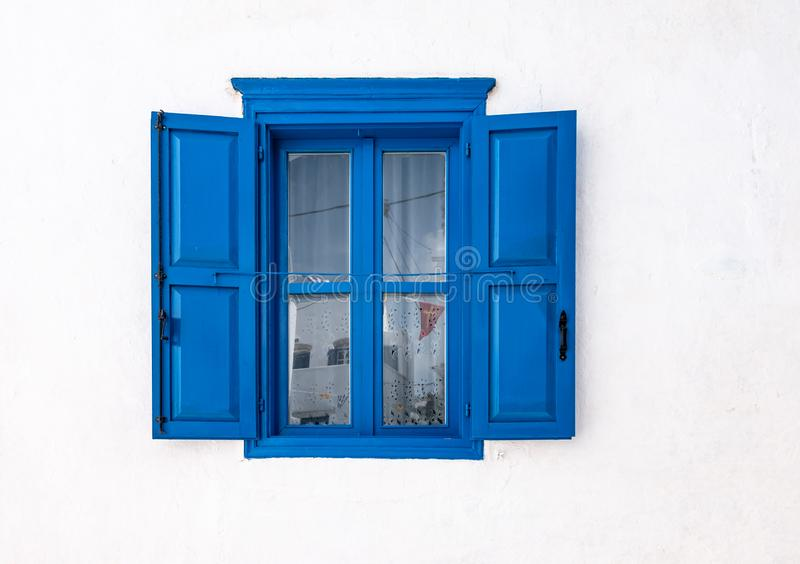 Blått fönster med öppna slutare och den vita väggen av det grekiska huset i Amorgos, Grekland royaltyfri foto