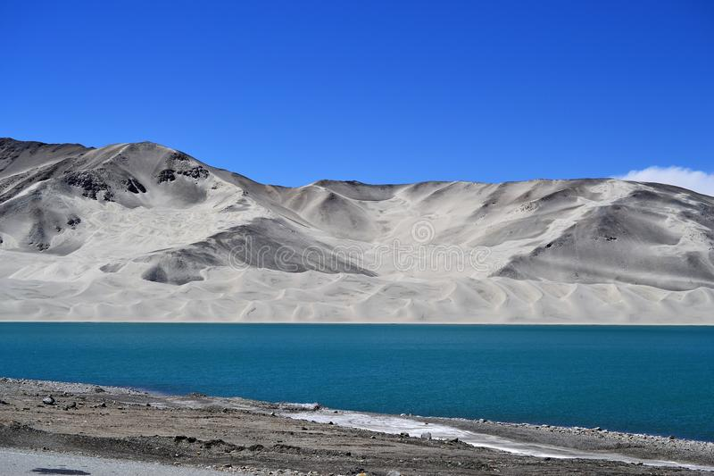 Blått för dyn för sand turkosoch vatten på Bulunkou sjön på den Karakoram huvudvägen, Xinjiang royaltyfria foton