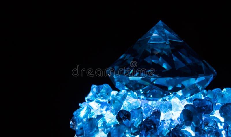 Blått gjord ljusare diamant på stenar fotografering för bildbyråer