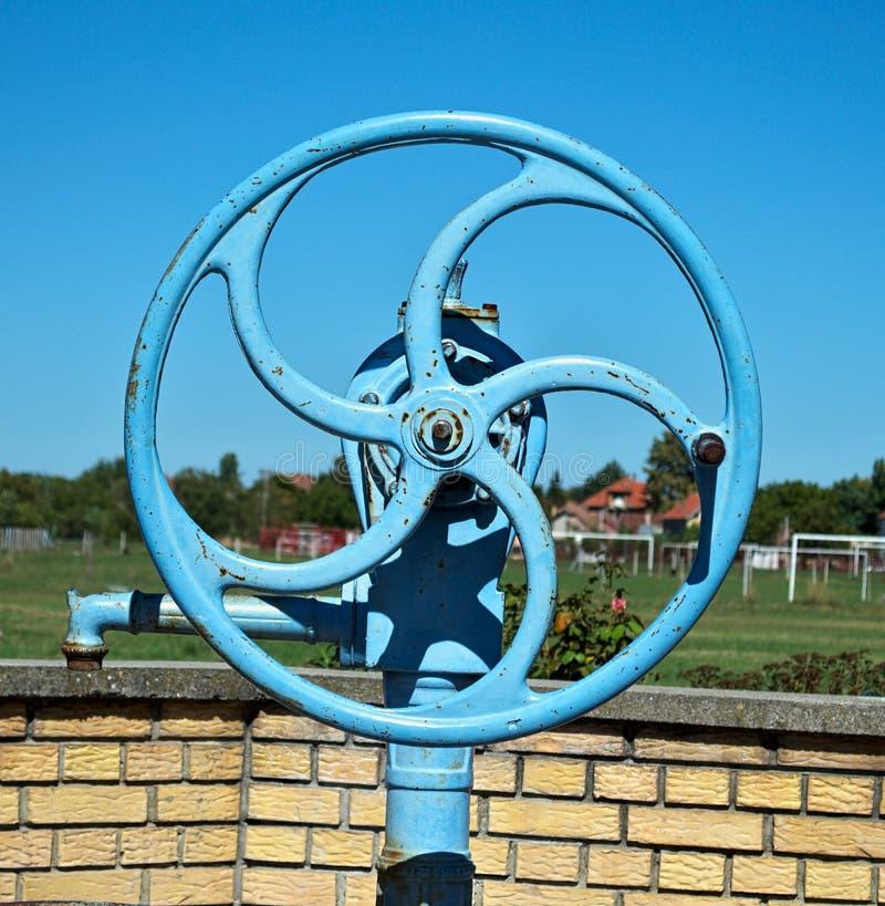 Blått hjul på den väl pumpen för vatten, slut upp royaltyfri bild