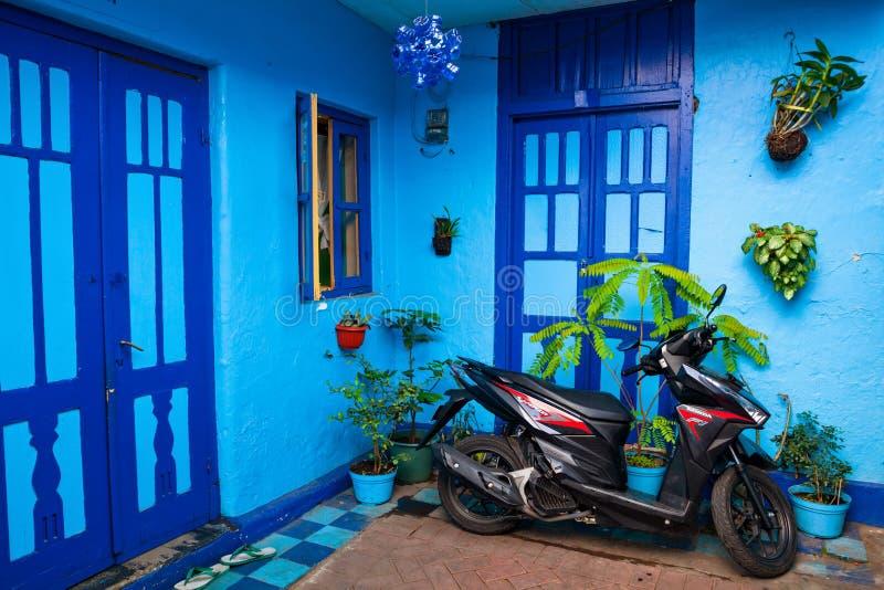 Blått hus med den parkerade mopeden i byn Kampung Biru Arema arkivbild