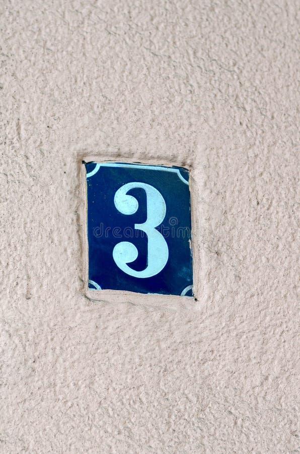 Blått keramiskt husnummer på en vit vägg royaltyfria bilder