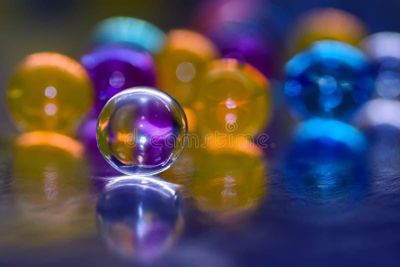 Blått-lilor orb med reflexion, mot en bakgrund av färgrika ballonger, abstrakt bakgrund fotografering för bildbyråer