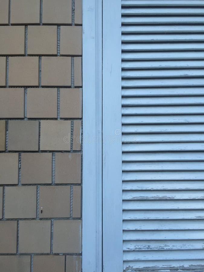Blått målad fönsterslutare med tegelplattor arkivfoton