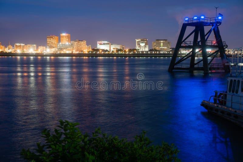 Blått Mississippi River som för skeppsdockaPilingssken flödar förbi Baton Rouge arkivfoto
