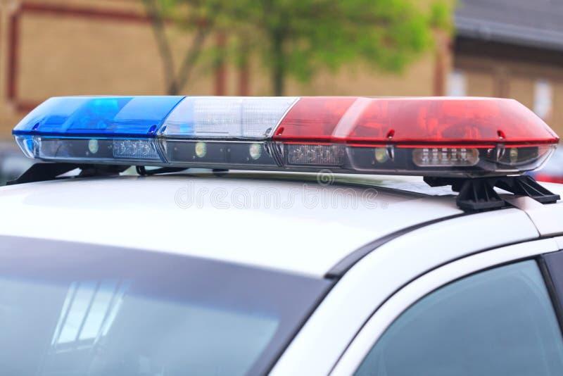 Blått och röda blinkande siren av polisbilen under väggspärret royaltyfri bild