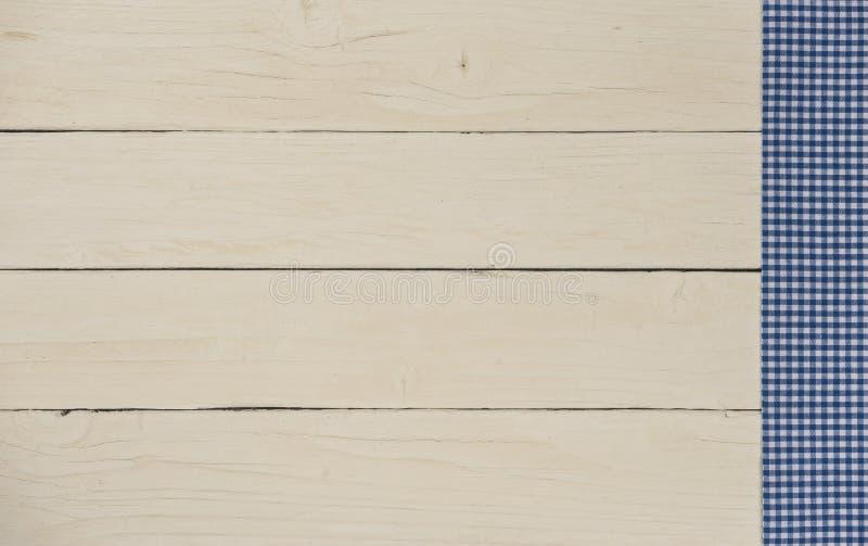 Blått och vit kontrollerade tabelltorkduken på en vit wood tabell royaltyfri bild