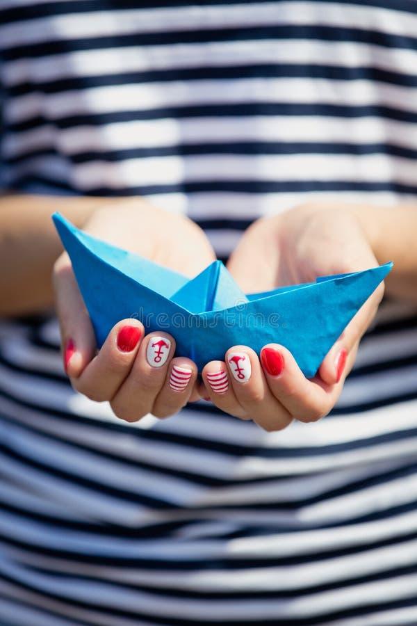 Blått pappers- skepp i kvinnas händer arkivbilder
