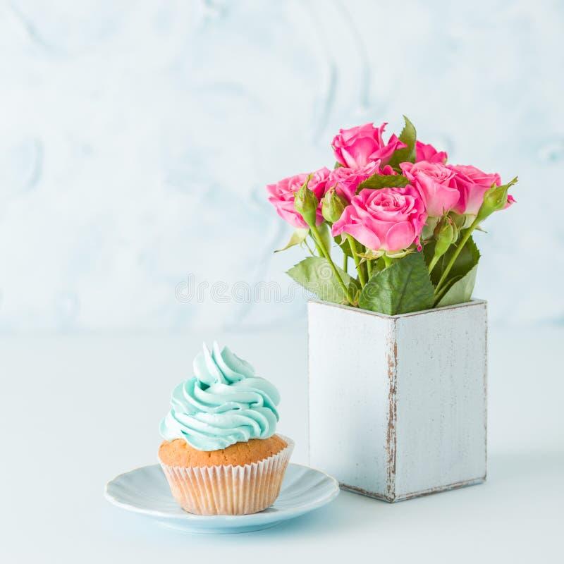 Blått pastellfyrkantbaner med muffin med den blåa garnering och buketten av rosa rosor i retro sjaskig chic vas royaltyfri foto