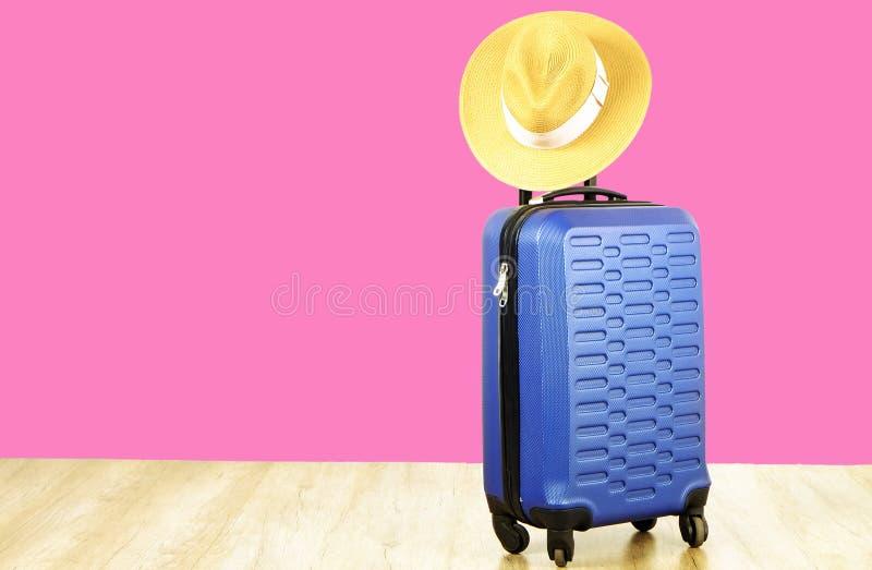 Blått plast- hårt skalbagage för singel med kvinnasugrörhatten som hänger på det fördjupade teleskopiska handtaget en resväska Re royaltyfria foton