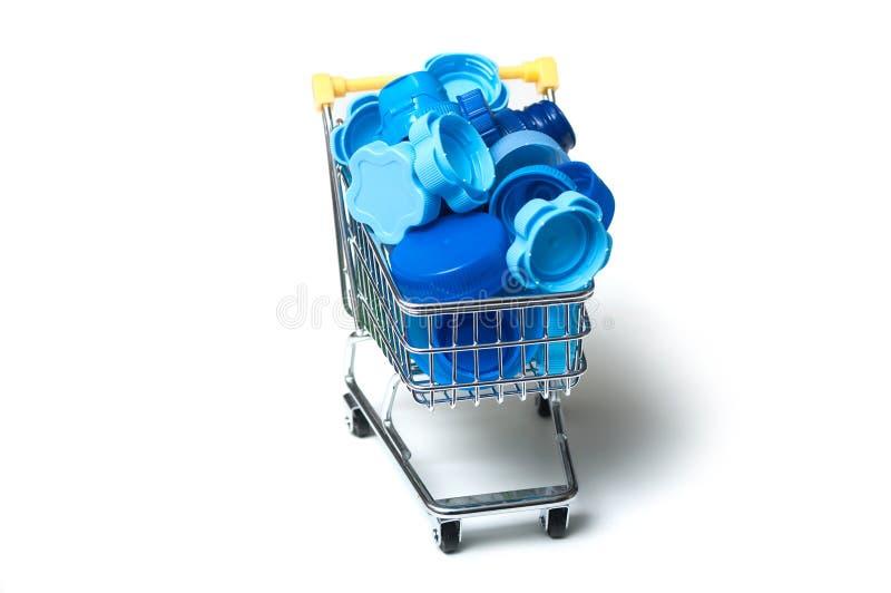 Blått plast- pluggar i den mini- supermarketspårvagnen - plast- förbrukningsbegrepp royaltyfri bild