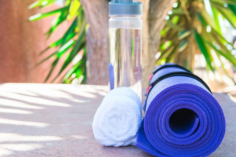 Blått rullande yoga Mat Bottle med den vita handduken för vatten på bakgrund för grönskapalmträdnatur solljus Avkopplingsommarmed arkivbilder