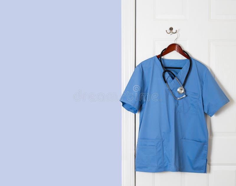 Blått skurar skjortan för den medicinska professionelln som hänger på dörr arkivbild