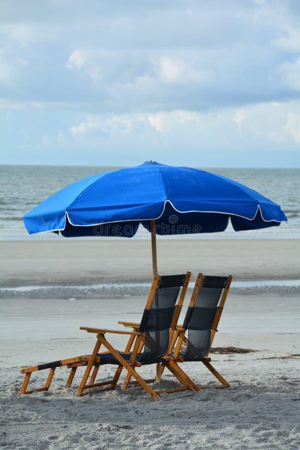 Blått sunbed för två med parasollen på den Coligny stranden av Hilton Head Island, South Carolina royaltyfria bilder