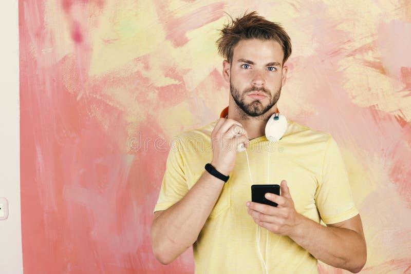 Blått synad stilfull hipster med smartphonen Musikalisk livsstil royaltyfria foton