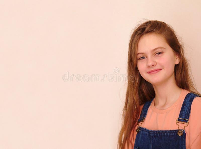 blått synade den bruna haired blyga flickan i grov bomullstvilloveraller Studiomodellskott royaltyfria foton