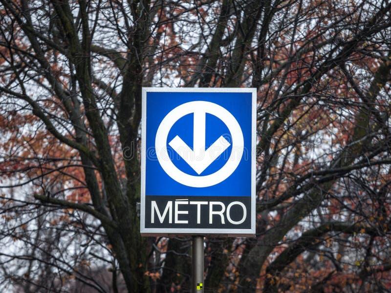 Blått tecken som indikerar en gångtunnelstation med dess särskiljande logo på det Montreal tunnelbanasystemet som klaras av av ST arkivfoto