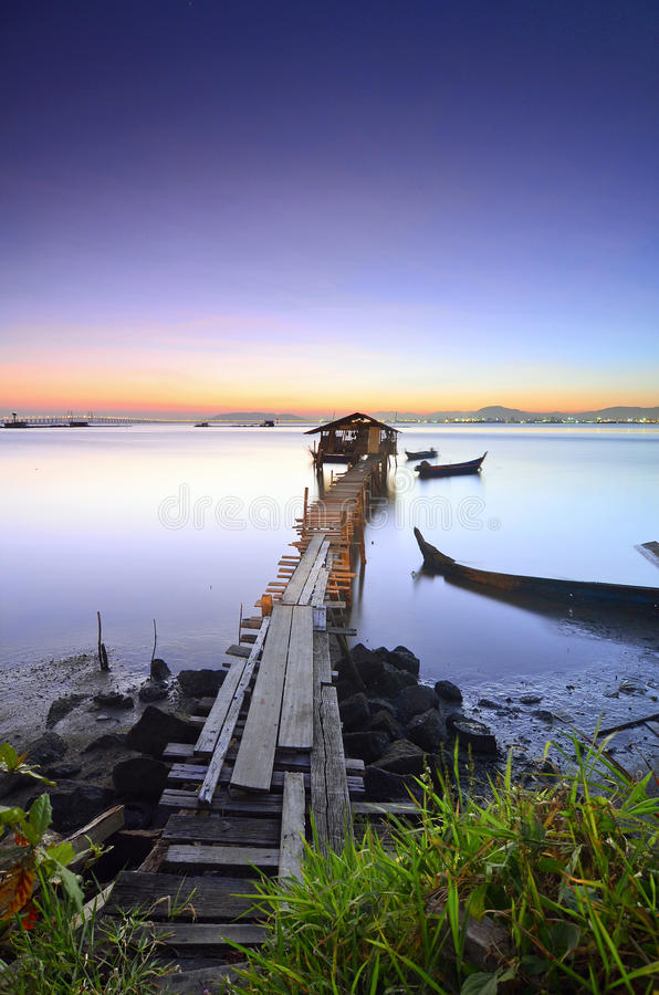Blått timmelandskap av den gamla övergav fiskarebryggan för sunris royaltyfri bild
