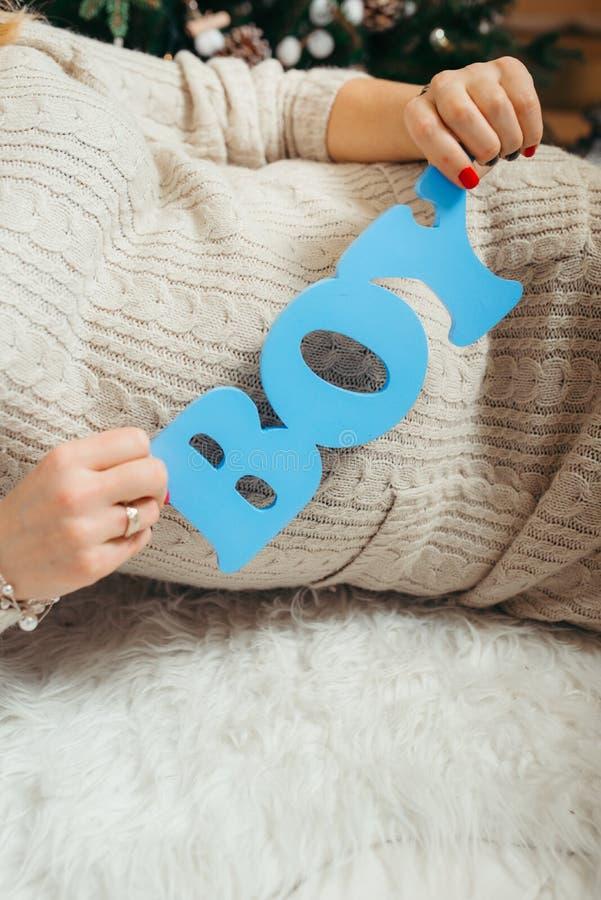 Blått trätecken `` pojke `` i händerna av gravida kvinnan som lägger på den vita fluffiga mattan royaltyfri fotografi
