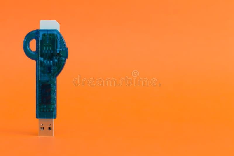 Blått USB pråligt minne på en orange bakgrund kortläsaren inkluderar royaltyfri fotografi